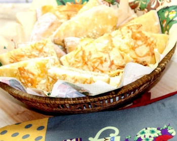 запеченные хачапури с брынзой в корзине, застеленной салфеткой, на столе
