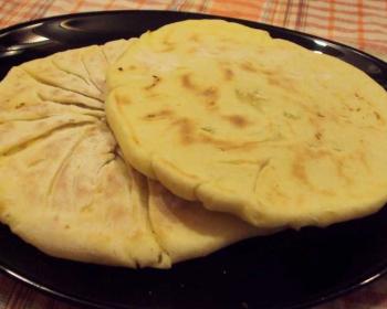 румяные хачапури с творогом, приготовленные на сковороде, лежат на черный тарелке