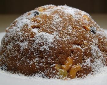 халава с орехами и изюмом, присыпанная кокосовой стружкой, на белой плоской тарелке