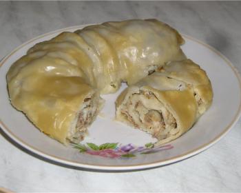 рулет с мясной начинкой из фарша и лука на белой плоской тарелке на столе