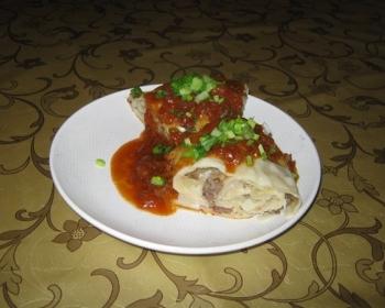 рулет из мяса с картошкой, политый подливой и украшенный рубленой зеленью, на белой плоской тарелке на столе, застеленном скатертью