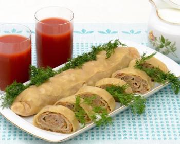 широкая продольная белая тарелка с ханумом, приготовленным в духовке, из лаваша, и нарезанным рулетом, рядом стоят два стакана с томатным соком и графин с соусом
