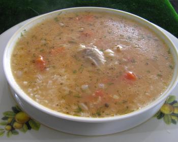 харчо из кусочков курицы, красного сладкого перца, риса, репчатого лука и зелени в белой тарелке на столе