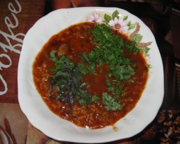 харчо из свинины с рисом и зеленью в белой тарелке на столе