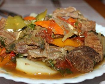 хашлама из кусочков говядины, картофеля, сладкого перца и зелени на белой тарелке