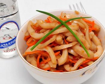 хе из кальмаров и осьминогов в миске на столе, на фоне бутылка водки