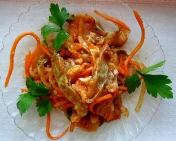 кусочки рыбы, перемешанные с морковью, луком и чесноком, украшенные петрушкой, в стеклянной миске на столе