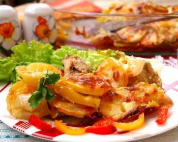 на круглой тарелке с узорами лежит хек, запеченный с картошкой в духовке, рядом на тарелке лежат свежие листья салата и полукольца болгарского перца