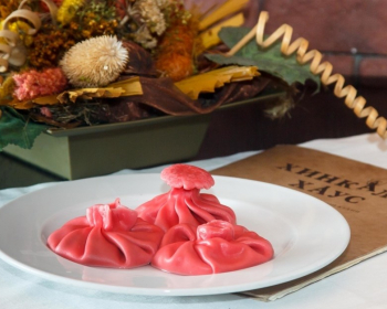 три розовые хинкали с картошкой на белой плоской тарелке на столе