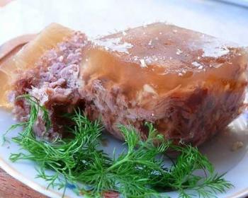холодец из свиной головы на тарелке с веточкой свежего укропа