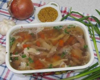 холодец из свиной рульки и курицы с кусочками моркови и зеленым луком в судочке, рядом лежат веточки зеленого лука, горчица в зернах в соуснице, две головки чеснока и репчатый лук