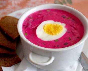холодник из свеклы с половинкой вареного яйца в суповой тарелке на столе с ломтиками черного хлеба