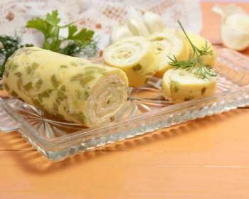 на прозрачной прямоугольной тарелке лежит яичный рулет с плавленным сыром, три кусочка рулета отрезанные лежат рядом, сверху лежит свежая зелень