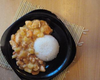 тушеное японское карри из кусочков куриного филе, картофеля и отварного риса в черной тарелке на столе