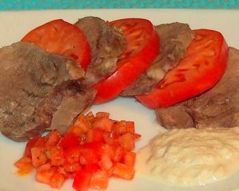 нарезанный ломтиками отварной говяжий язык с ломтиками помидора, два соуса рядом на тарелке