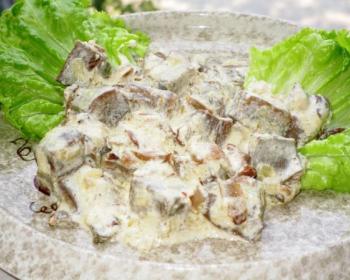 тушеные кусочки говяжьего языка с грибами, политые сметаной, на плоской тарелке с листьями салата
