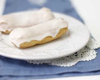 два эклера с масляным кремом и белой глазурью в тарелке на столе
