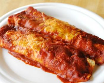 две лепешки энчилады с начинкой внутри, политые томатной пастой, на белой плоской тарелке на столе