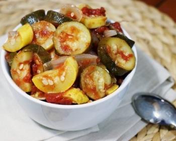 тушеные кабачки с помидорами в глубокой белой тарелочке на белой салфетке, рядом лежит ложка