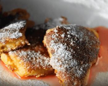 на тарелке лежит кайзершмаррн, нарезанный кусочками и присыпанный сахарной пудрой