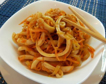кальмары по-корейски с морковью в тарелке на столе, рядом палочки для еды