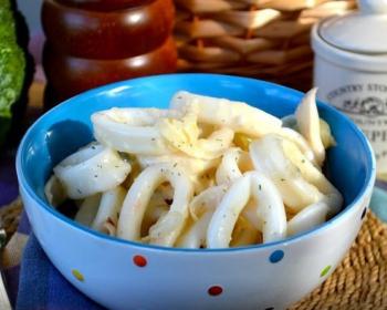тушеные кольца кальмаров с луком в глубокой голубой тарелке на столе, застеленном скатертью, рядом вилка