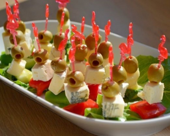 маленькая тарелочка с канапе с оливками и сыром на красных шпажках на столе