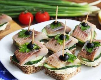 на белой тарелке лежат канапе с селедкой из черного хлеба со свежими огурцами, маслинами и зеленью, рядом лежат одно канапе с сельдью, два помидора черри, пучок зеленого лука и лимон