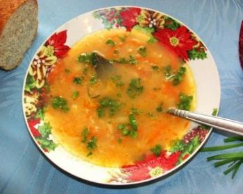 капустняк с квашеной капустой, зеленью, морковью и лавровым листом в глубокой тарелке с ложкой на столе, застеленном скатертью, на фоне ломтик белого хлеба