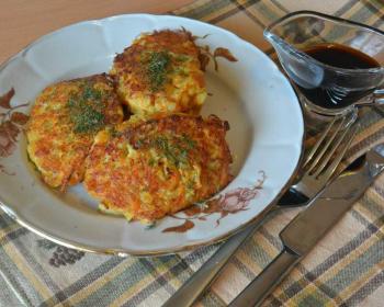 три капустно-морковные котлеты, присыпанные укропом, в тарелке на столе, рядом соусница с соевым соусом, вилка и нож