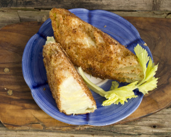 два жареные капустные шницели на синей тарелке с зеленью на деревянной разделочной доске на столе