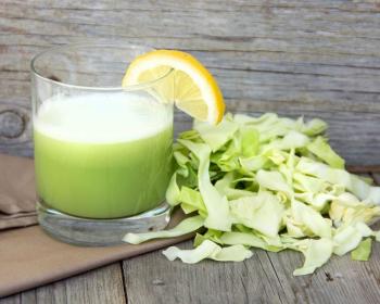 квас из капусты в стеклянном стакане с ломтиком лимона на столе, рядом измельченная белокочанная капуста
