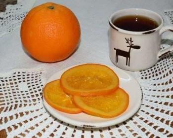 карамелизированные апельсины, нарезанные кружочками, лежат на блюдце, рядом целый апельсин и чашка с чаем