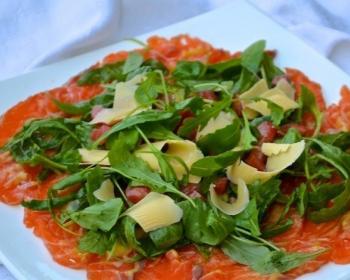 сырые ломтики лосося, покрытые рукколой и сыром, на плоской тарелке на столе