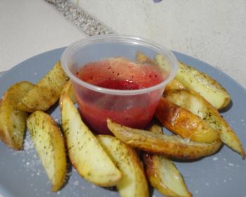 дольки запеченного молодого картофеля с клюквенным соусом в тарелке
