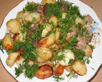 картофель, запеченный в рукаве в духовке, со свиными ребрышками, лежит на большом белом блюде, сверху измельченная зелень укропа
