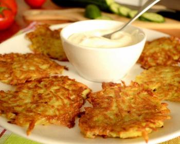 картофельные драники, приготовленные в духовке, лежат кругом на белой тарелке, внутри на тарелке стоит соусница с соусом