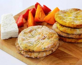 круглые картофельные лепешки рядом кусочек сыра и помидор, нарезанный дольками на большой деревянной доске