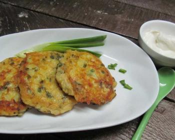 картофельные оладьи с сыром и зеленью на большой белой тарелке, пластиковая зеленая ложка и сметана в соуснице на деревянном столе