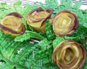 картофельные розочки в искусственной зелени на тарелке