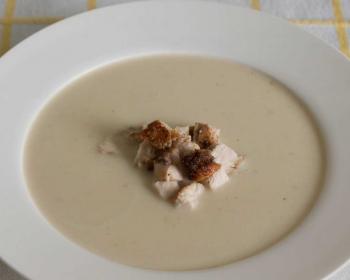 суп-пюре из картофеля с кусочками жареной куриной грудки в белой тарелке на столе, застеленном скатертью