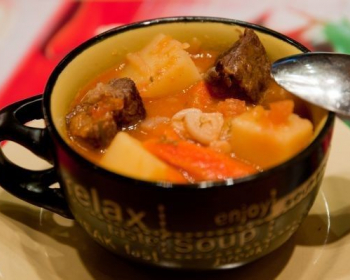 каурдак из тушеных кусочков мяса с картофелем и красным сладким перцем с чесноком в кружке с ложкой на столе