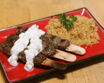 три кебаба из говядины с гарниром и соусом на тарелке