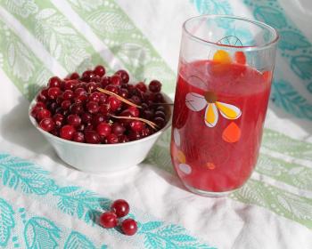 ягоды клюквы в пиале, клюквенный сок в стакане с узором на столе, застеленном тканевой скатертью
