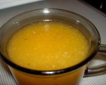 оранжевый кисель из кураги и изюма в кружке на столе, застеленном с катертью