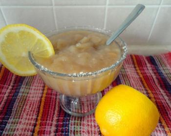 кисель из сухофруктов с долькой лимона в стеклянной пиале с ложкой на столе, застеленном скатертью