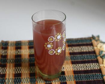 прозрачный стакан с узором, наполненный киселем из варенья, на бамбуковой салфетке на столе