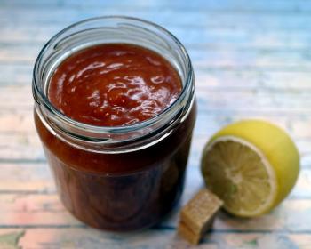 китайский кисло-сладкий красный соус в стеклянной баночке на столе, рядом разрезанный лимон
