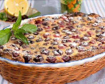 французский десерт клафути с вишней в плетеной корзинке на столе, украшенный зеленью