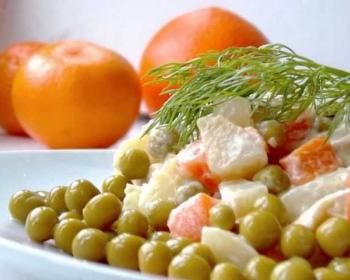 классической оливье с курицей и горошком, украшенное веточкой укропа, на тарелке на столе, мандарины на фоне